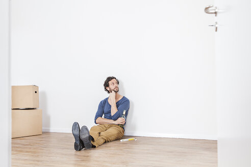 Man sitting on floor and looking away - FMKF000569
