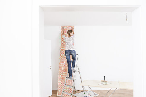 Woman sticking wallpaper on wall - FMKF000631