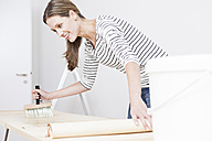 Woman applying glue on wallpaper - FMKF000634