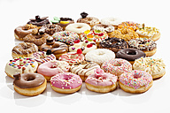 Variety of doughnuts topped with icing and sprinkles on white background - CSF017907