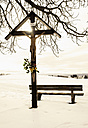 Germany, Bavaria, Crucifix and bench in snow - MOF000181