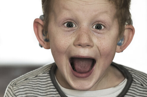 Austria, Boy with hearing aid laughing - CW000020