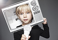 Portrait of boy head in paper TV with paper microphone against grey background - ED000015