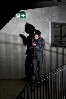 Germany, Bavaria, Young man smoking in dark corner - MAE006278