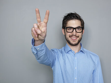 Businessman doing peace sign, smiling - STKF000228