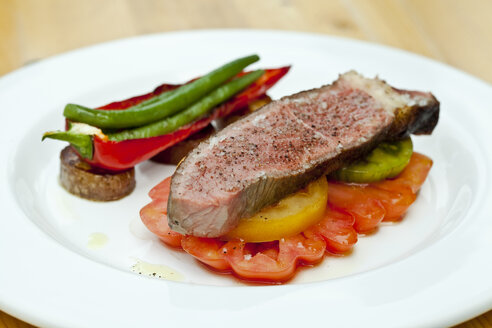 Germany, Duesseldorf, Plate of grilled beef with tomatos and paprika, close up - KVF000010