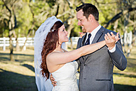 USA, Texas, Young wedding couple looking at each other, smiling - ABAF000801
