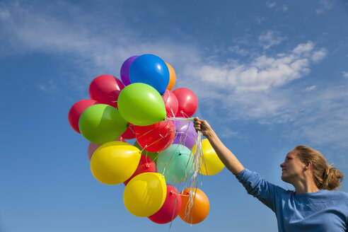 Germany, Bavaria, Mature woman holding colourful balloons against sky - HSIF000284