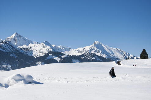 Austria, Woman hiking at Tannheim Alps in winter - UMF000610