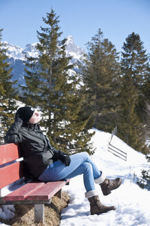 Austria, Woman relaxing on bench at Tannheim Alps - UMF000596