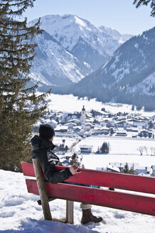 Austria, Woman relaxing on bench in Tannheim Alps - UMF000599