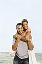 Spain, Mid adult man giving piggy back ride to woman, smiling - SKF001222