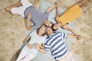 Spain, Family lying on beach at Palma de Mallorca, smiling - SKF001186