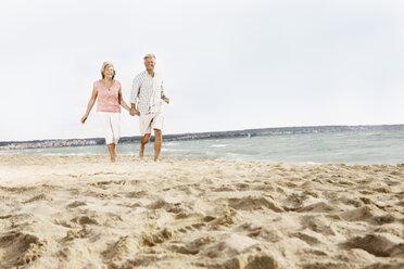 Spain, Senior couple walking on beach at Palma de Mallorca - SKF001180