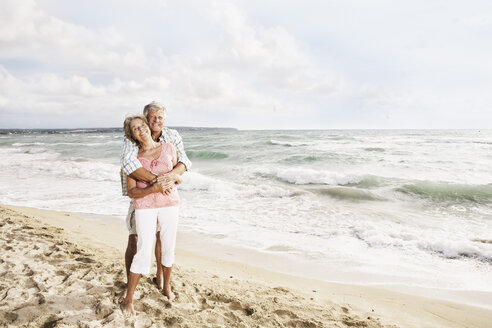 Spain, Senior couple embracing on beach at Palma de Mallorca - SKF001183