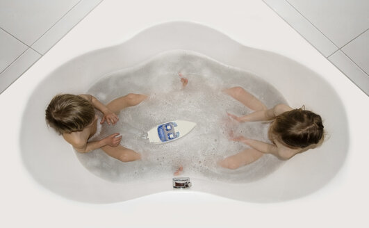Austria, Boy and girl sitting in bathtube and playing with boat - CW000029