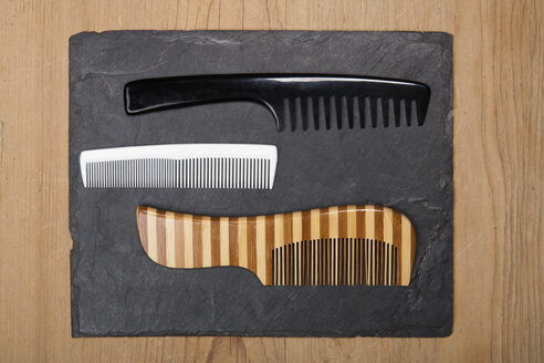 Various hair combs on slate board, close up - TDF000044