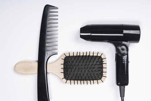 Hair dryer, comb and brush on white background, close up - TDF000048