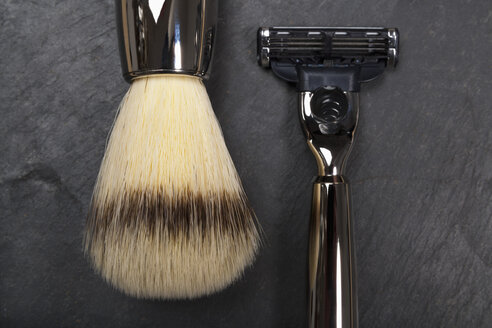 Shaving brush, razor and razor blade on slate board, close up - TDF000023