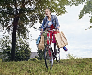 Germany, Cologne, Young woman on bicycle with shopping bags - RHYF000353