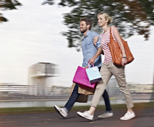 Germany, Cologne, Young woman and mid adult man with shopping bags - RHYF000357