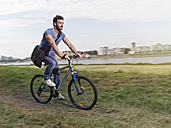 Germany, Cologne, Young man riding bicycle - RHYF000372