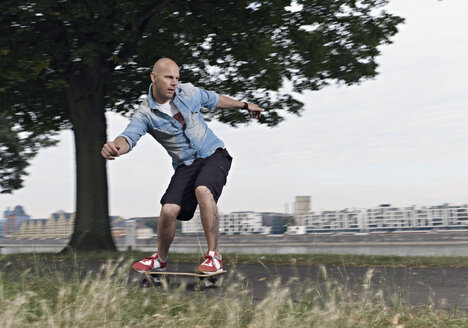 Germany, Cologne, Mature man skating on skateboard - RHYF000362