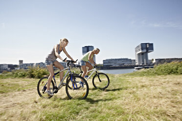 Germany, Cologne, Two Young women cycling bicycle - RHYF000368