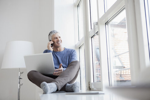 Germany, Bavaria, Munich, Mature man talking on mobile and using laptop, smiling - RBF001221