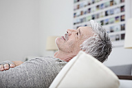 Germany, Bavaria, Munich, Mature man relaxing on couch, smiling - RBF001236