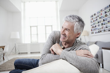 Germany, Bavaria, Munich, Mature man sitting on couch, smiling - RBF001206