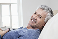 Germany, Bavaria, Munich, Portrait of mature man relaxing on sofa, smiling - RBF001212