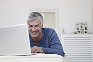 Germany, Bavaria, Munich, Portrait of mature man using laptop on couch, smiling - RBF001274