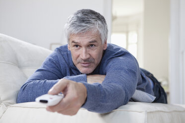 Germany, Bavaria, Munich, Mature man changing channels with remote control - RBF001222