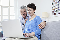 Germany, Bavaria, Munich, Couple using laptop at home, smiling - RBF001251