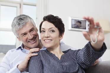 Germany, Bavaria, Munich, Couple taking self portrait of themselves at home, smiling - RBF001242