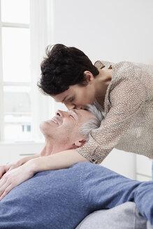 Germany, Bavaria, Munich, Woman kissing on mans forehead, smiling - RBF001290