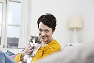 Germany, Bavaria, Munich, Portrait of mid adult woman with cat on couch, smiling - RBF001298
