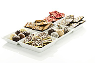 Variety of chocolates and pralines in bowl on white background - MAEF006290