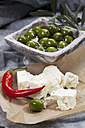 Bowl of green olives in olive oil  with sheep's cheese and chili on textile, close up - CSF018508