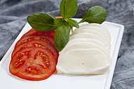 Slices of mozzarella cheese, tomatoes and basil herb on chopping board, close up - CSF018526