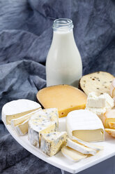 Varieties of cheeses on chopping board with bottle of milk on textile - CSF018808