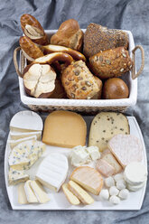 Varieties of cheeses on chopping board and basket of breads on textile - CSF018631