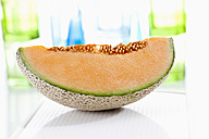 Slice of cantaloupe melon on chopping board, close up - CSF018652