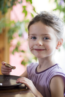 Germany, Bavaria, Girl eating toast with chocolate cream, portrait - SARF000002