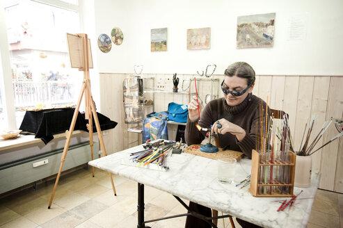 Germany, Bavaria, Mature woman making glass beads - RNF001196