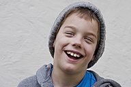 Boy laughing against wall, close up - LV000012