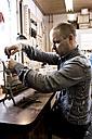 Germany, Bavaria, Mid adult man repairing piano - RN001205