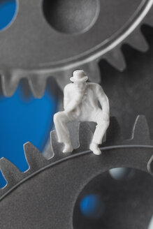 Figurine sitting on gear wheels, close up - CSF018834