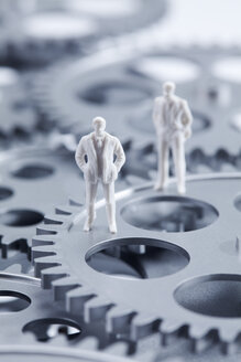 Figurine of businessmen standing on gear wheels, close up - CSF018819